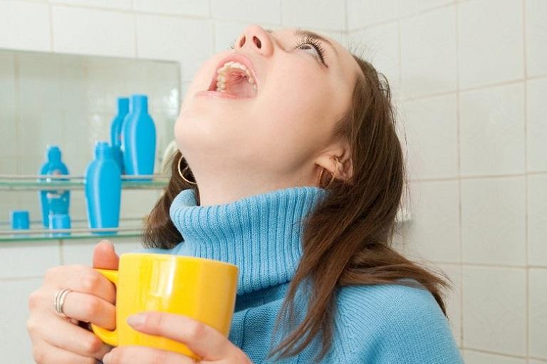 Ngửa cổ khi súc miệng để nước muối thấm vào sâu mọi ngóc ngách của khoang miệng